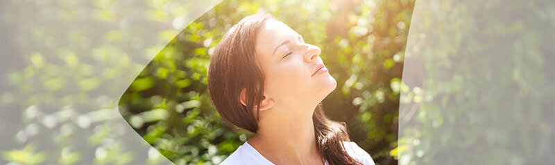 Young woman with eyes closed taking a breath of fresh air