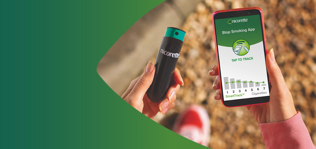 Hand holding a phone with Nicorette QuickMist SmartTrack Nicotine Mouth Spray