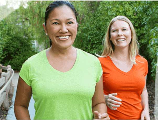 Two ladies on a walk being active, healthy, and smiling.